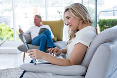 Smiling woman with laptop and man using technology. Smiling women with laptop and men using technology at home Stock Photography