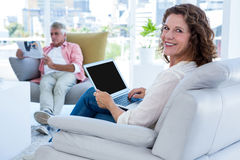 Smiling woman with laptop while mature man reading newspaper Stock Photo