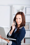 Smiling woman with a laptop and mobile Stock Photos
