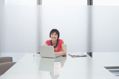 Smiling Woman With Laptop In Modern Cubicle. Smiling thoughtful young woman sitting with laptop in modern cubicle at office Stock Images