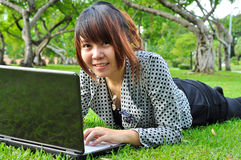 Smiling woman with laptop in nature Stock Photo