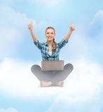 Smiling woman with laptop and showing thumbs up Royalty Free Stock Images