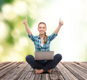 Smiling woman with laptop and showing thumbs up Stock Photos