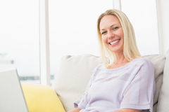 Smiling woman with laptop sitting on sofa Stock Photography