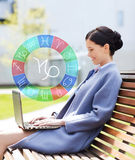 Smiling woman with laptop and zodiac signs in city stock photo