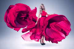 Smiling woman in large flying pink dress Royalty Free Stock Photo