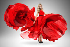 Smiling woman in large flying red dress Stock Image