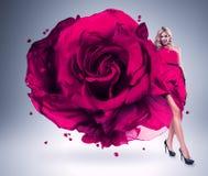 Smiling woman in large pink rose dress. In studio Stock Image