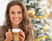 Smiling woman with latte macchiato near christmas tree Royalty Free Stock Images