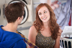 Smiling Woman In Laundromat. Smiling Woman flirts with man in laundromat stock image