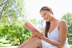 Smiling woman on the lawn reading a book Stock Images