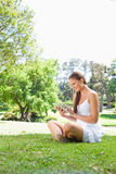 Smiling woman on the lawn with a tablet computer Royalty Free Stock Photos