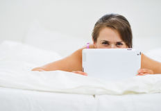 Smiling woman laying in bed and hiding tablet PC. Smiling young  woman laying in bed in room and hiding tablet PC Royalty Free Stock Photography