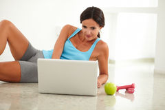 Smiling woman laying and browsing on her computer Royalty Free Stock Photo