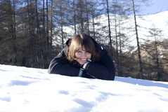 Smiling woman laying in snow Royalty Free Stock Image