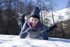 Smiling woman laying in snow Stock Images