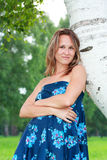 Smiling woman leaned against a birch tree Stock Photo