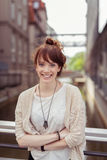 Smiling Woman Leaning Against Bridge Railings Stock Photo