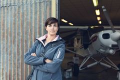 Smiling woman leaning against the hangar walls Royalty Free Stock Image