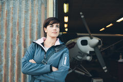 Smiling woman leaning against the hangar walls. Smiling young woman leaning against the hangar metallic rusty walls, light aircraft on the background Royalty Free Stock Photos