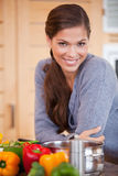 Smiling woman leaning against the kitchen counter Royalty Free Stock Photos
