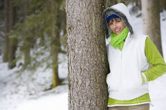 Smiling woman leaning against tree trunk in woods Royalty Free Stock Photography