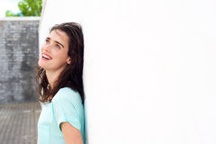 Smiling woman leaning against white wall looking up Royalty Free Stock Image