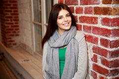 Smiling woman leaning on the brick wall Stock Photo