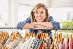Smiling woman leaning on clothes rail Royalty Free Stock Image