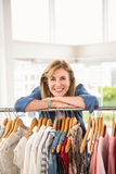 Smiling woman leaning on clothes rail Stock Image