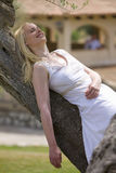 Smiling woman leaning on olive tree trunk with eyes closed Royalty Free Stock Image