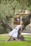 Smiling woman leaning on olive tree trunk Royalty Free Stock Photography