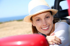 Smiling woman leaning out of the car window Royalty Free Stock Images