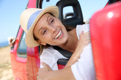 Smiling woman leaning out of the car window Royalty Free Stock Photography