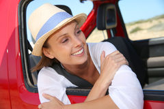 Smiling woman leaning out of the car window Stock Image
