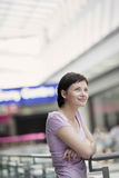 Smiling Woman Leaning On Railing In Shopping Centre Stock Images