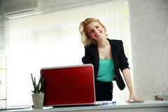 Smiling woman leaning on the table. Young beautiful smiling woman leaning on the table in office Royalty Free Stock Photography