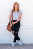 Smiling woman leaning on white wall with purse. Full body portrait of smiling woman leaning on white wall with purse Stock Photo
