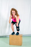 Smiling woman in leg brace stands on wood box. Near white canvas while wearing bright pink top Royalty Free Stock Image