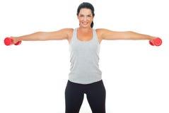 Smiling woman lifting barbell Stock Photo