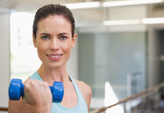 Smiling woman lifting blue dumbbell Royalty Free Stock Image