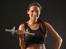 Smiling woman lifting a dumbbell Royalty Free Stock Photos