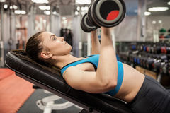Smiling woman lifting dumbbells while lying down Stock Images