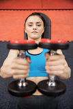 Smiling woman lifting dumbbells while lying down Stock Photos