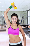 Smiling woman lifting hand with dumbbell Stock Photography