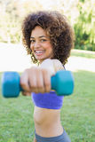 Smiling woman lifting hands weights Stock Image