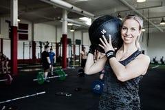 Smiling Woman Lifting Medicine Ball. Portrait of smiling women lifting medicine ball in fitness center Royalty Free Stock Photo
