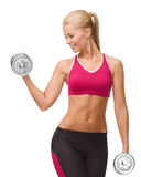 Smiling woman lifting steel dumbbell Royalty Free Stock Images