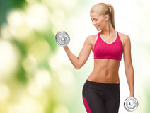 Smiling woman lifting steel dumbbell Royalty Free Stock Photo