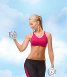 Smiling woman lifting steel dumbbell Stock Photo